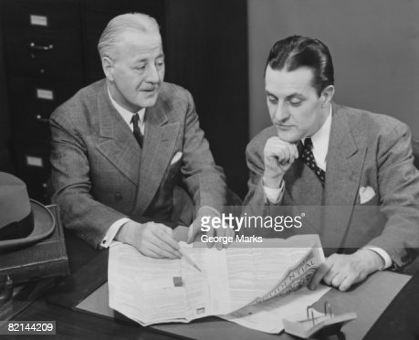 Two businessmen discussing document at desk, (B&W) : Stock Photo