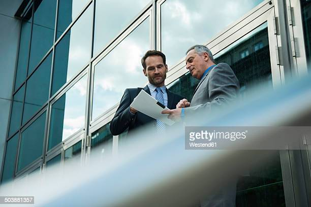 Two businessmen discussing documents outside office building