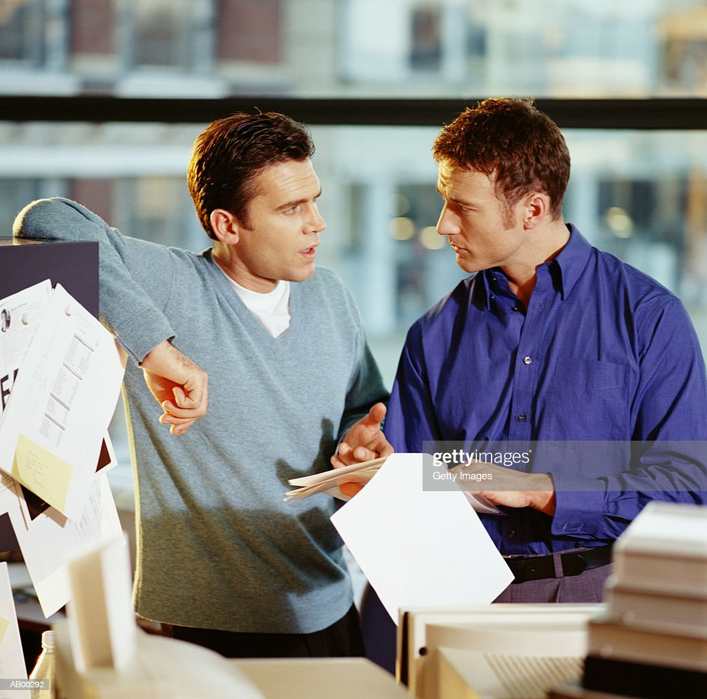 Two businessmen discussing paperwork in office : Stock Photo