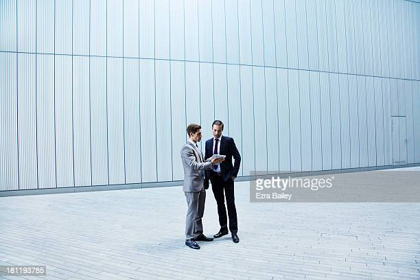Two businessmen discussing plans on tablet.