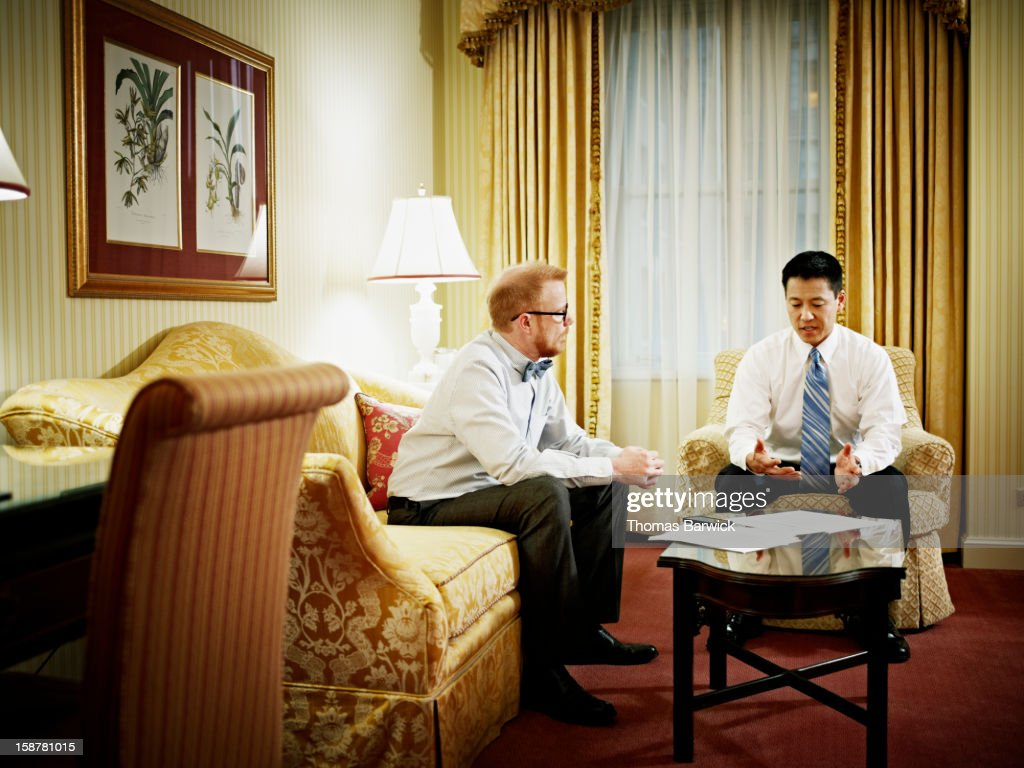 Two businessmen discussing project in hotel room : Stock Photo