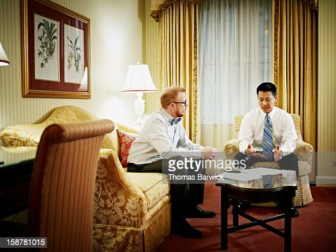 Two businessmen discussing project in hotel room : ストックフォト