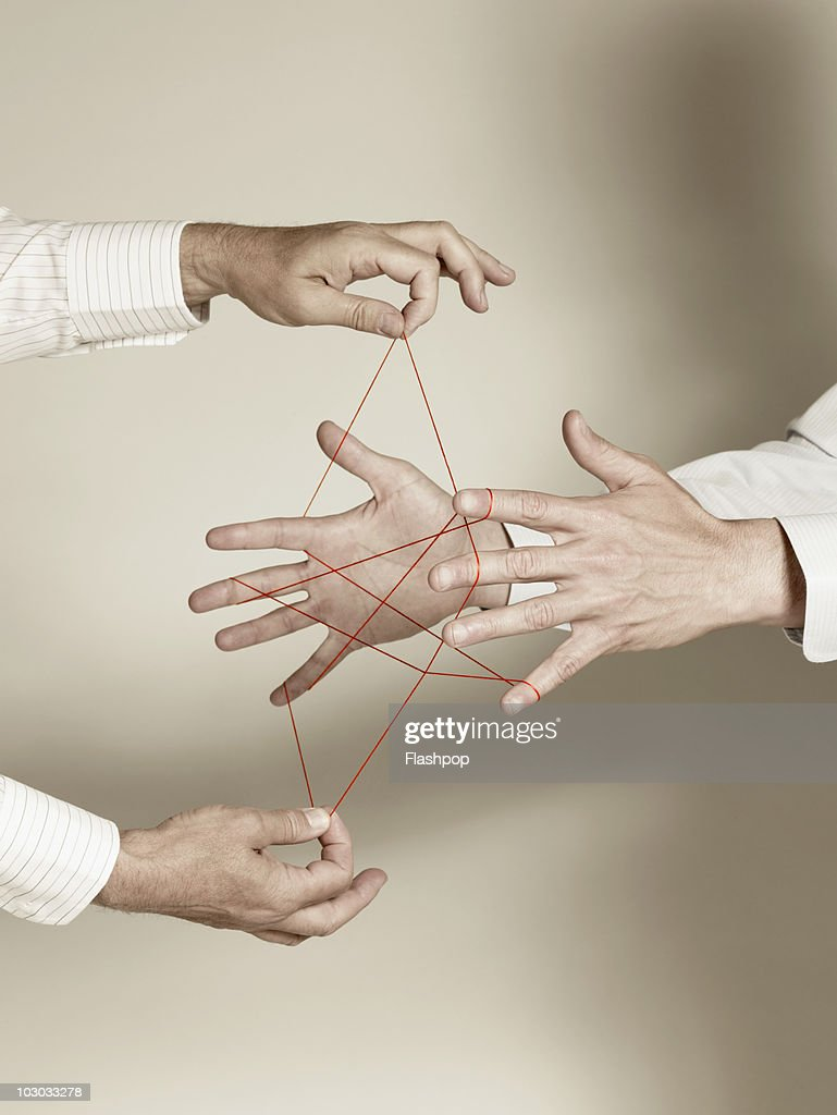 Two businessmen doing cat's cradle : Stock Photo