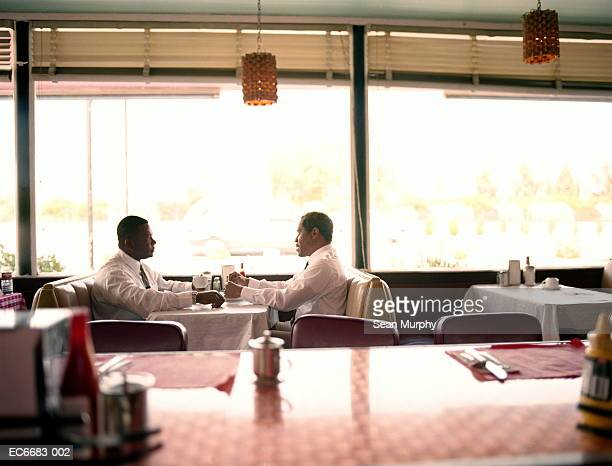 Two businessmen drinking coffee in diner