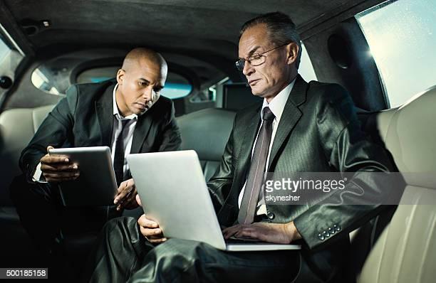 Due uomini d'affari si recano al lavoro e con tecnologia wireless.