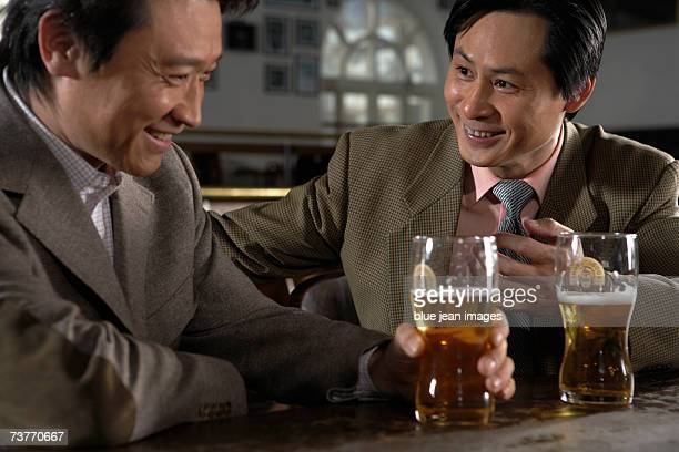 Two businessmen enjoy a drink at a bar
