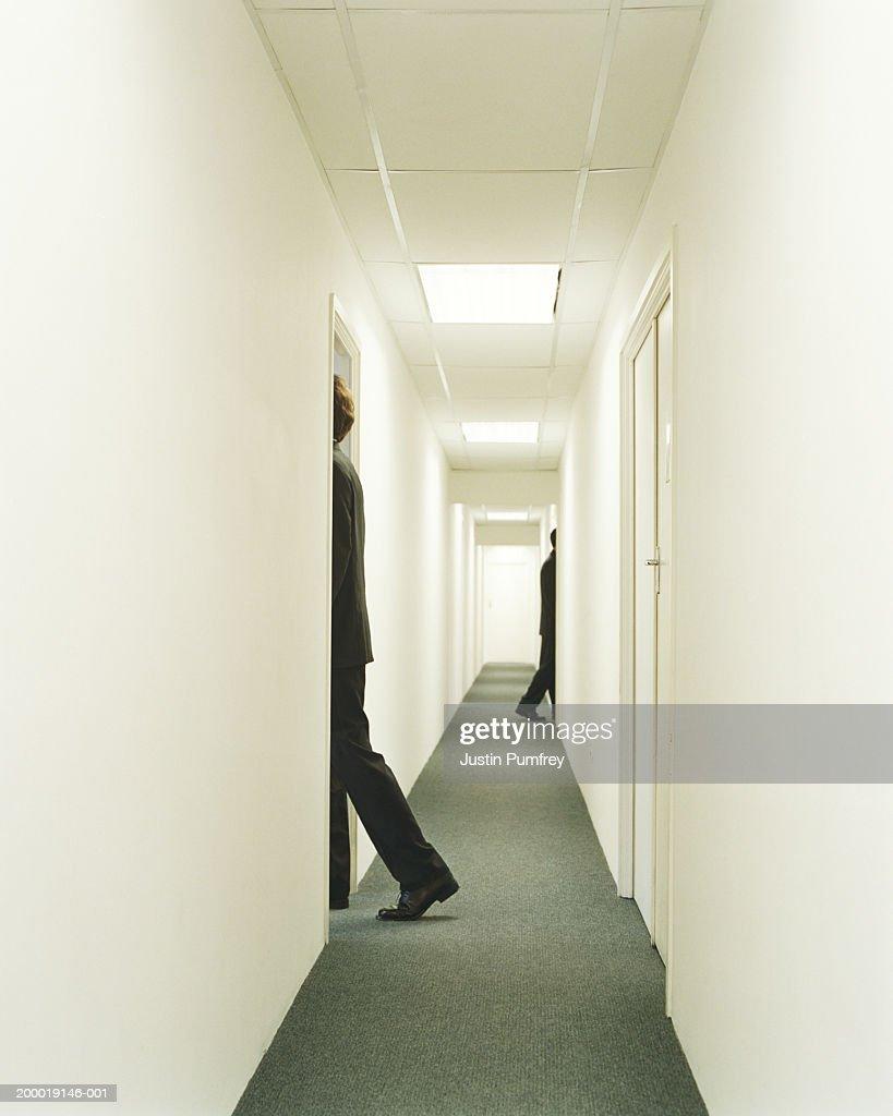 Two businessmen entering doorways in corridor