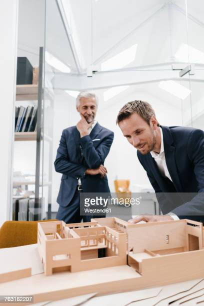 Two businessmen examining architectural model in office
