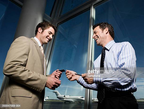 Two businessmen exchanging cards in airport lounge, smiling, low angle view