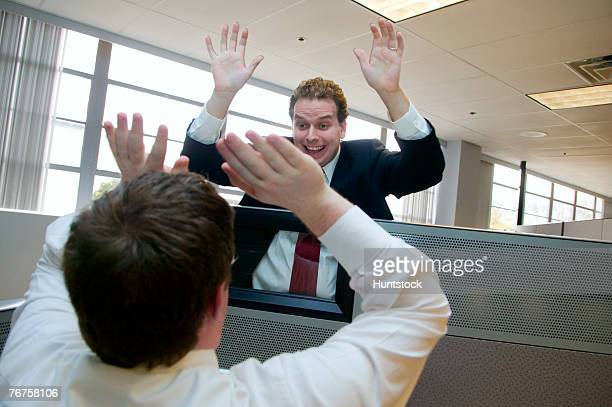 Two businessmen exchanging high-five over cubicle wall