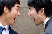 Two businessmen face to face, yelling each other, close up, China, Beijing