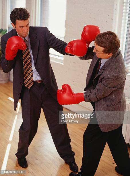 Two businessmen fighting in empty room, wearing boxing gloves