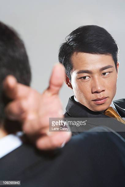 Two businessmen fighting on grey background