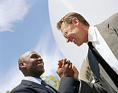 Two businessmen greeting each other in street, smiling, low angle view