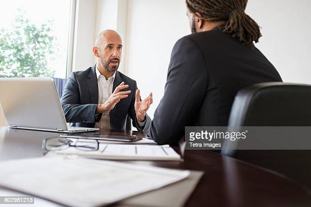 Two businessmen having discussion at desk in office