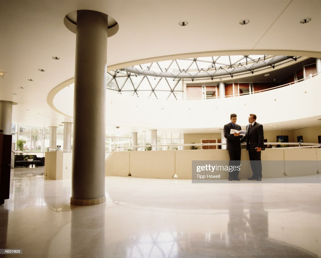 Two businessmen having discussion in building lobby : Stock Photo