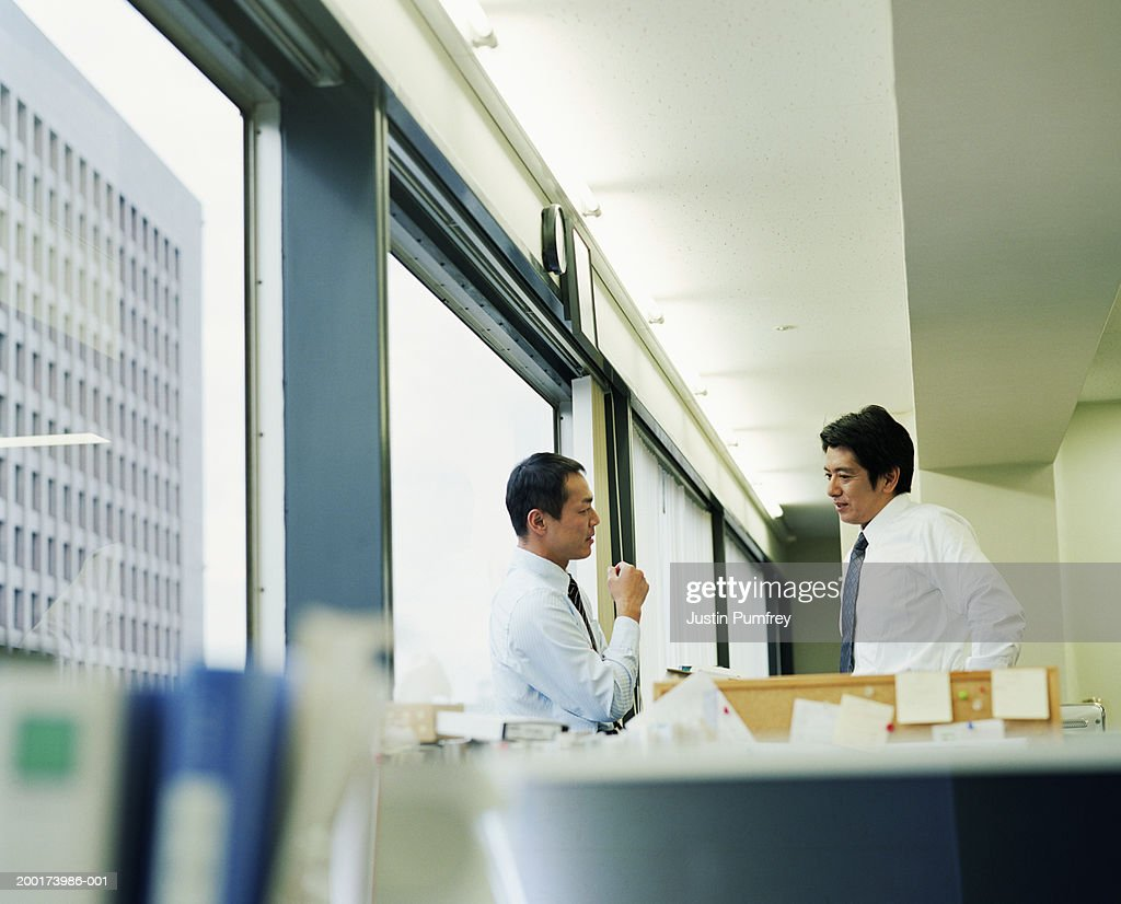 Two businessmen having discussion in office, side view : Stock Photo