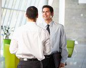 Two Businessmen Having Informal Meeting In Modern Office