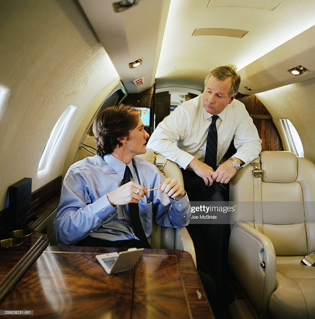 Two businessmen having meeting on corporate jet : Stock Photo