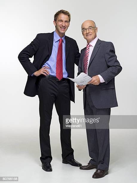 Two businessmen holding construction plan, smiling, portrait