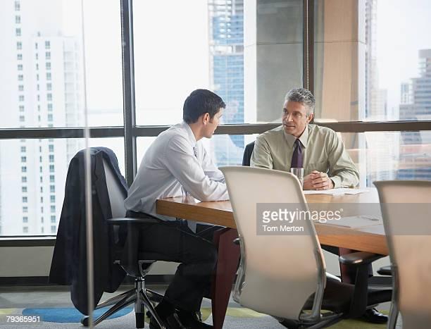 Due uomini d'affari in una sala per assemblee da grandi finestre