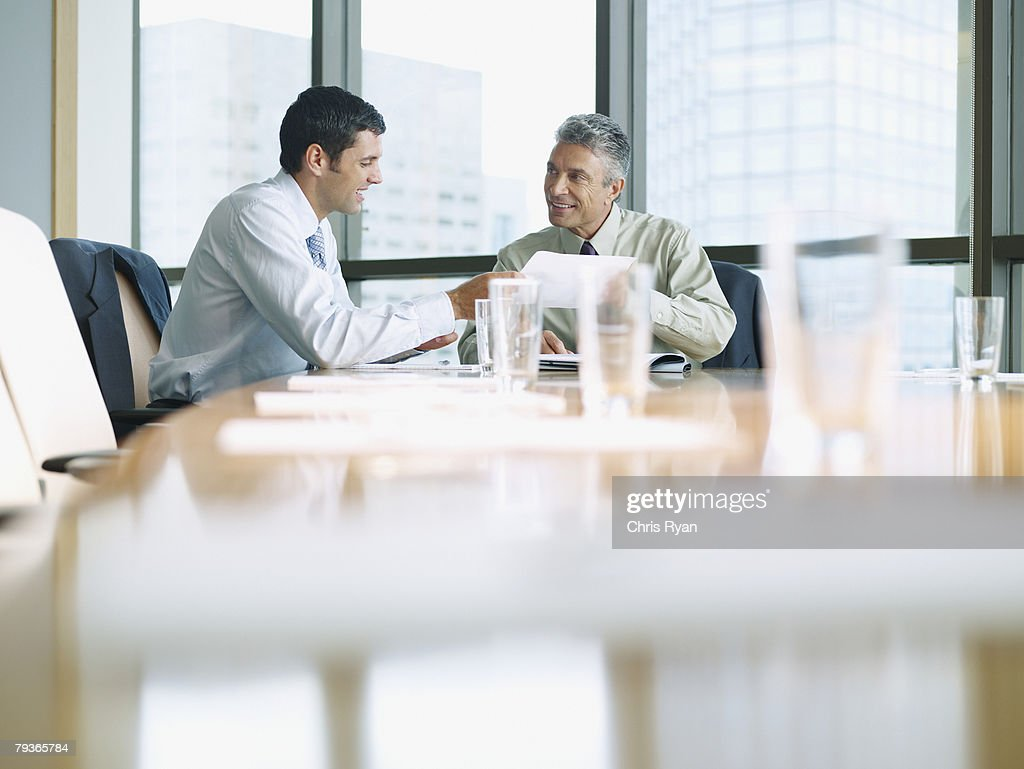 Two businessmen in a boardroom working