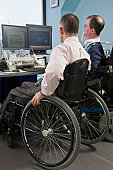 Two businessmen in a wheelchair working in an office