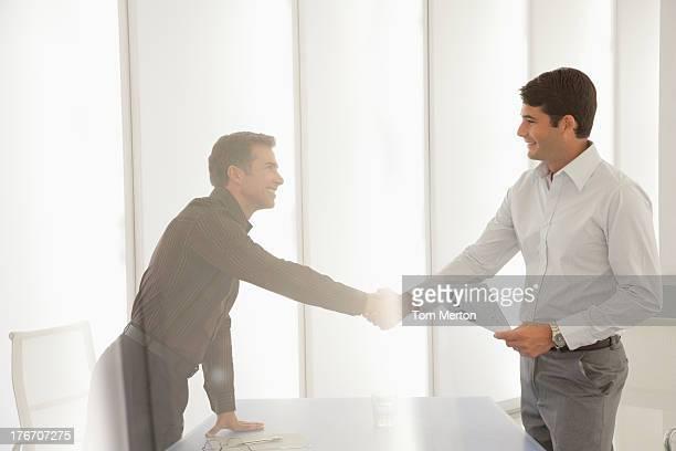 Dois empresários na sala de reuniões dar um aperto de mão