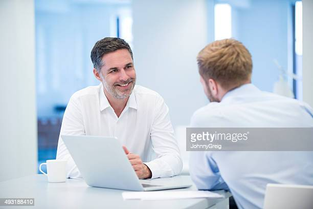 Two businessmen in discussion around laptop computer