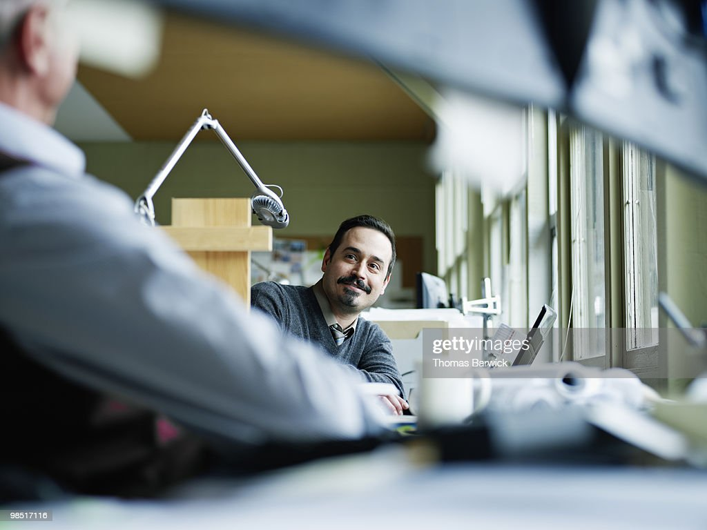 Two businessmen in discussion at workstation : Stock Photo