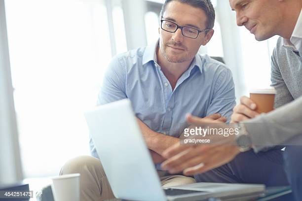 Two businessmen in discussion near a laptop