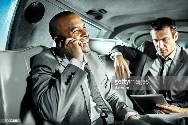 Two businessmen in gray suits in limousine