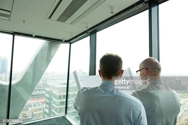 Two businessmen in office looking at blueprint