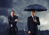 Two businessmen in rain