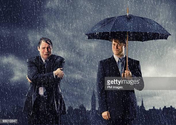 Two businessmen in rain