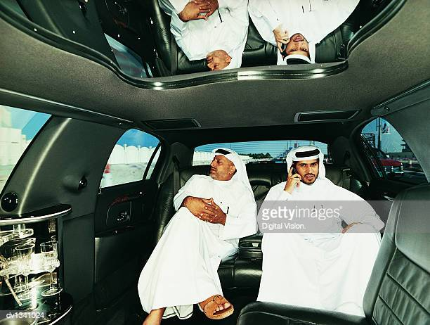 Two Businessmen in Traditional Middle Eastern Dress Sitting in the Back Seat of a Limousine