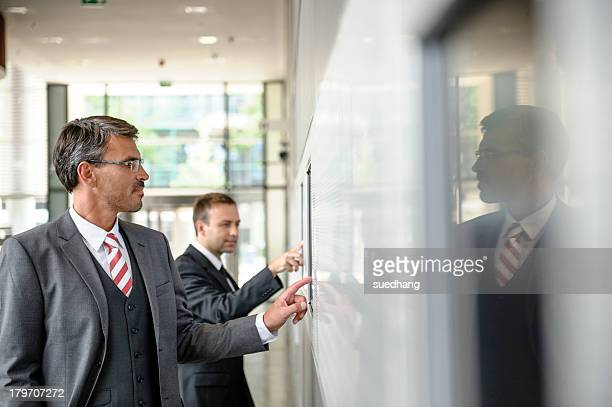 Two businessmen interacting with touch screens