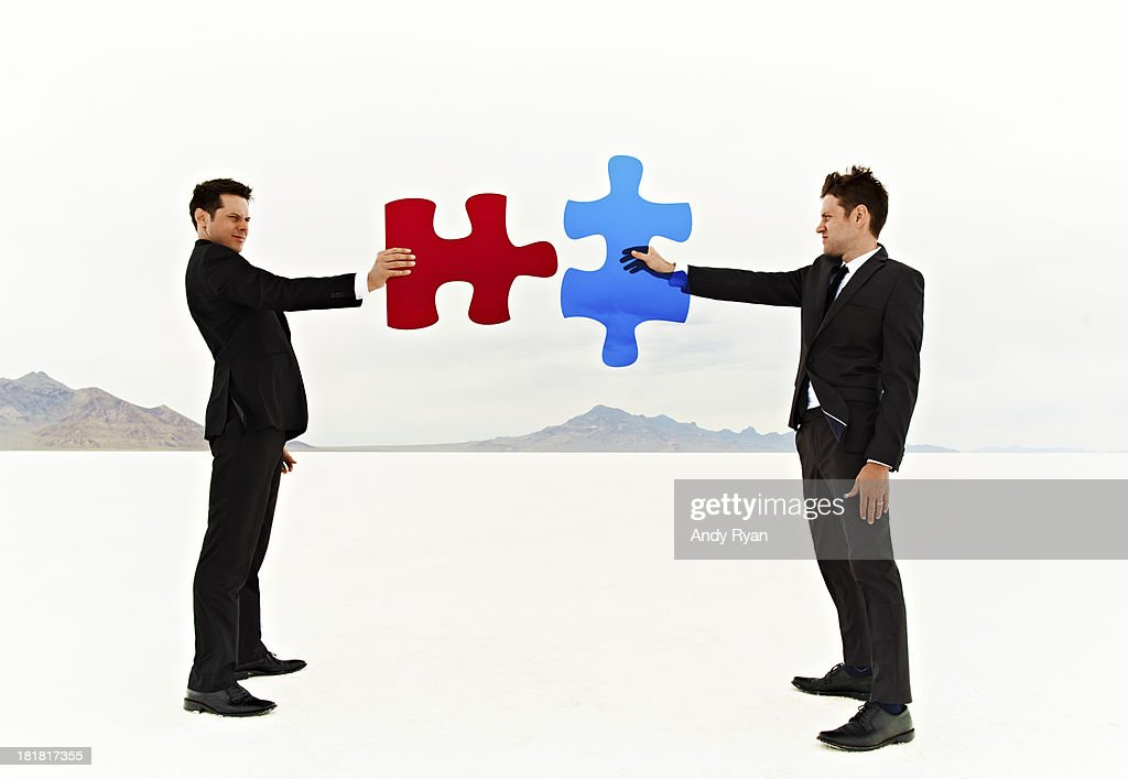 Two businessmen join colored puzzle pieces.