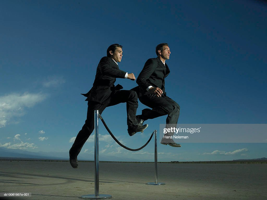 Two businessmen jumping over velvet rope barrier, low angle view : Stock Photo