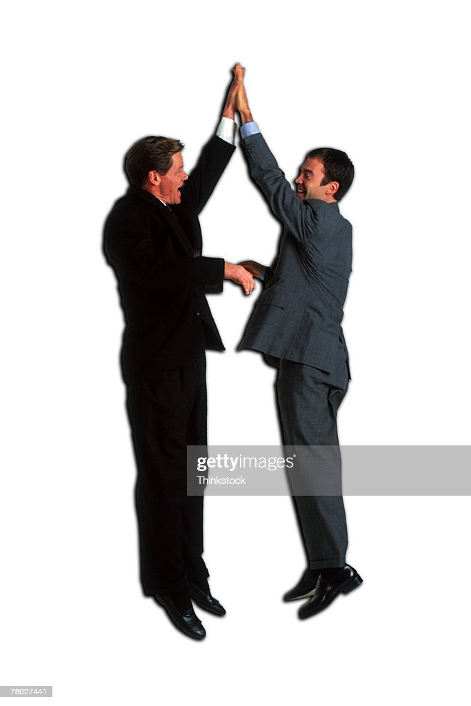 Two businessmen jumping up and slapping hands. : Stock Photo