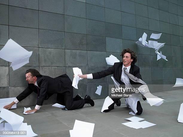 Two businessmen kneeling on pavement, grabbing paper blowing in wind