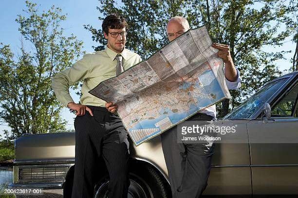 Two businessmen leaning against car, reading map