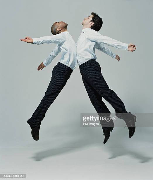 Two businessmen leaping into each other, side view