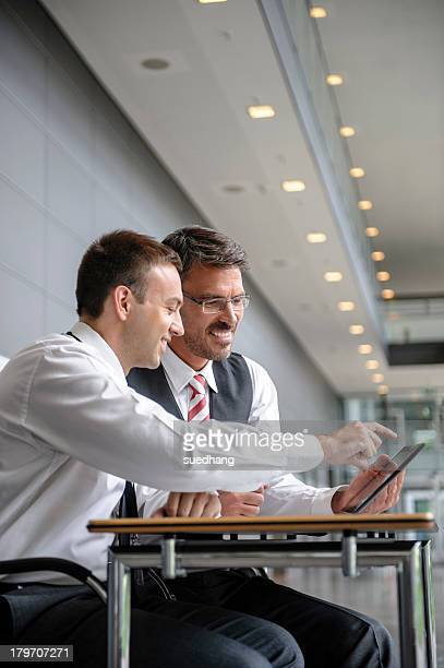 Two businessmen looking and pointing at digital tablet