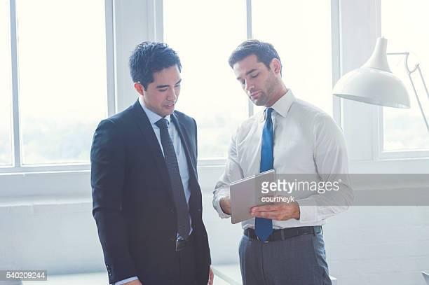2 つのビジネスマンので、デジタルタブレットを持っている。