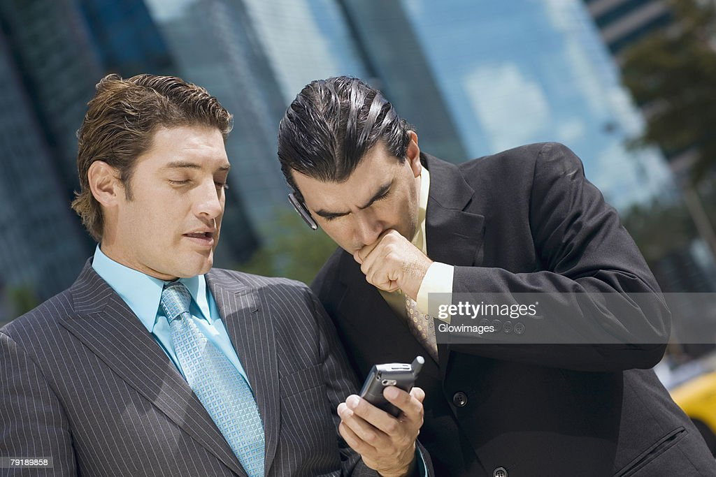 Two businessmen looking at a hand held device : Foto de stock