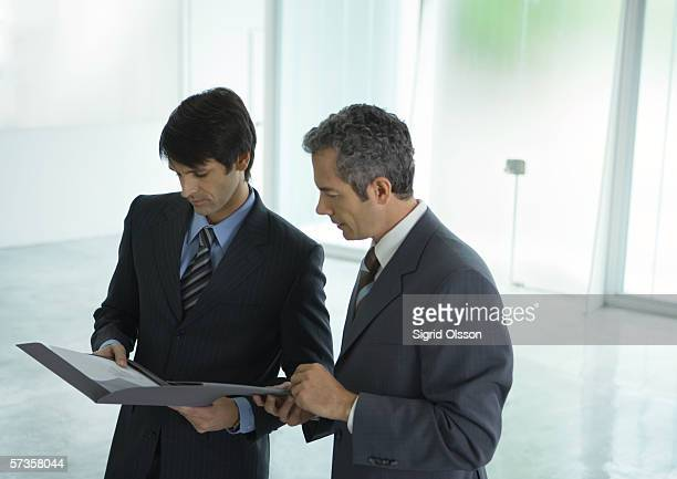 Two businessmen looking at file in lobby