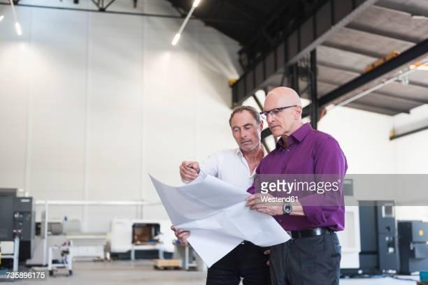 Two businessmen looking at plan in factory shop floor
