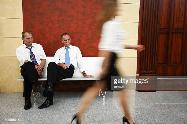 Two businessmen looking at woman's legs