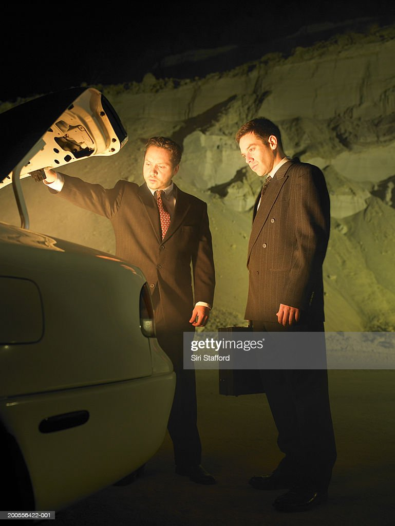 Two businessmen looking into glowing trunk of car : Stock Photo
